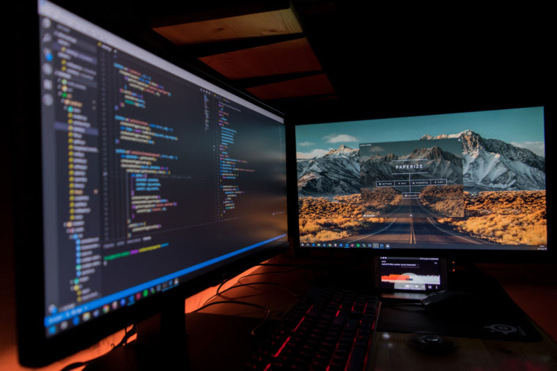 Computer scene at night with website development code on screen
